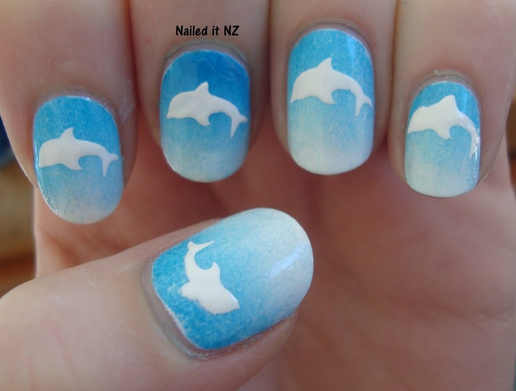 White dolphin diving on each nail of your hands in this dolphin nail art.  White dolphin on sky blue base looks really good. - 15 Delightful Dolphin Nail Art To Slay The Summer