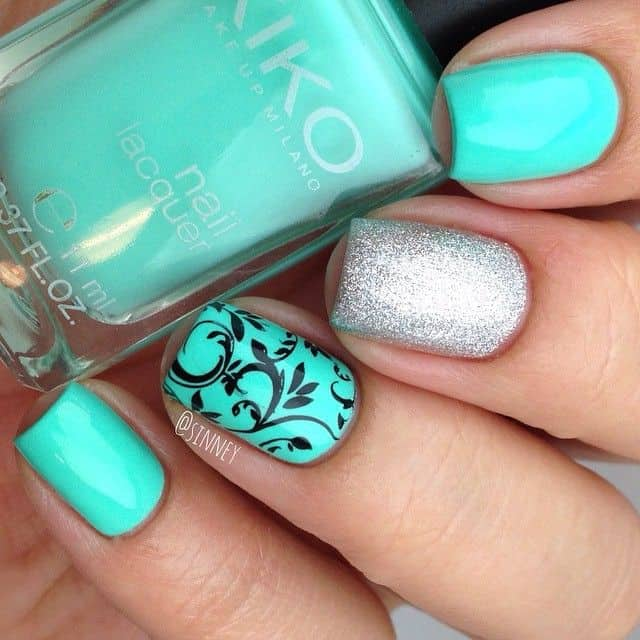 black floral design on mint green nail