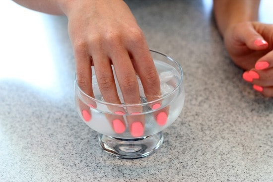 Dipping the chipped nails in ice-cold water
